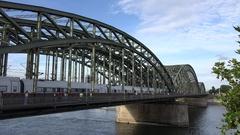 4K Train traffic and pedestrian cross Hohenzollern bridge Koln landmark barge Stock Footage