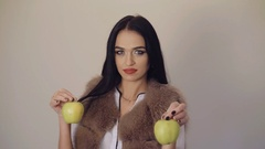 Cute girl holding a juicy green pears in hands, posing and smiling to camera 4K Stock Footage