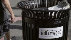 People walking past garbage can with Hollywood Entertainment District sign LA Stock Footage