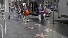 Asian couple walking Walk of Fame father husband pushing stroller Hollywood LA Stock Footage