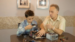 Dad teaches his son a teenager, what's inside the computer, video card Stock Footage