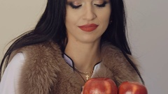 Passionate girl in furry jacket posing with two red apples. Slowly Stock Footage