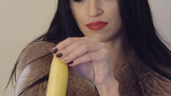 Passionate brunette peeling a big banana and looking to camera. Slowly Stock Footage