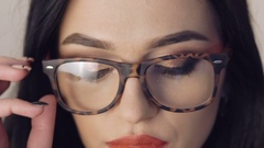 Close up of female face, girl undressing glasses and looking to camera Stock Footage