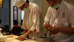 A team of cooks is making dumplings, one of them is kneading the dough. Stock Footage