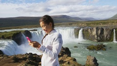 Tourist taking selfie photo with smart phone by Godafoss waterfall on Iceland Stock Footage