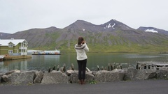 Tourist on Iceland taking photo wearing icelandic sweater in Siglufjordur Stock Footage