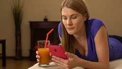Young beautiful attractive woman lying on a sofa, drinking juice and browsing on Stock Footage