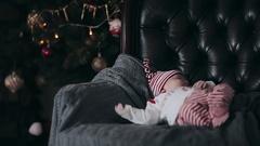Newborn baby sleeping in a chair near the Christmas tree Stock Footage