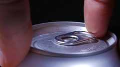 Macro close up of lid as hand opens a canned drink using tab Stock Footage