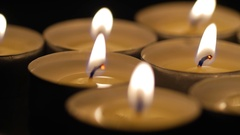 Macro close up of lit small candles rotating around 2 Stock Footage