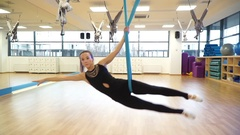 Coach makes gymnastic exercise moving from hammock to fly yoga on the floor Stock Footage