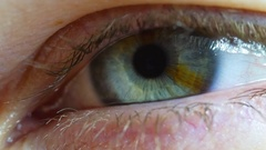 Macro close up of eye lid opening to reveal pupil and iris Stock Footage