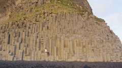 Iceland tourist travel woman on basalt columns on Reynisfjara black sand beach Stock Footage