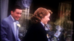 Well dressed people exit taylor shop & head to wedding, 3803 vintage home movie Stock Footage