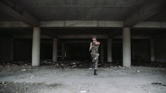 Sexy muscular man dancer in military clothes and dark glasses dances. Long shot Stock Footage