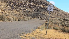 Nevada state line boundary marker on the side of a lonely gravel road, 3805 Stock Footage