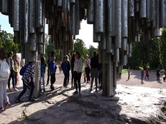 Children discover Sibelius Monument, girl stand up with head in pipe Stock Footage