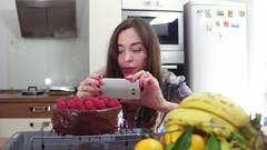 Young woman making photos of her freshly cooked cake. Steadicam 4K video Stock Footage