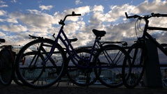 Citybikes attached to handrail, silhouetted view against cloudy evening sky Stock Footage