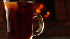 Cinnamon sticks falls into a beautiful mug of mulled wine Stock Footage