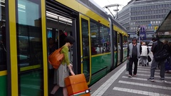 Asian woman come inside modern tram, doors closing and vehicle depart from stop Stock Footage