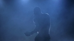 Strong muscular body of a boxer in silhouette and slow motion Stock Footage