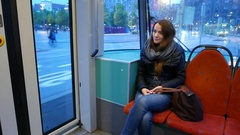 Tired but pleased traveller ride at rear of tramway, dusk city seen outdoor Stock Footage