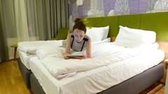 Woman lie on twin bed, look to small tablet, typical evening in hotel Stock Footage