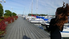 Slim woman come away along wooden pier, sunny day at yacht marina Stock Footage