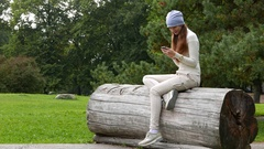 Hipster woman sit on large log in park, stare to smartphone, texting Stock Footage