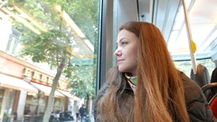 Woman look out tram window, coach begin to move, bright street outside Stock Footage