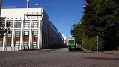 Tram drive at uphill way, empty street, building at one side, park at another Stock Footage