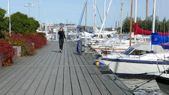 Young woman come towards along planked pier, listen music, sunny day Stock Footage