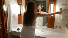 Woman use blow-dryer at bathroom, stand in towel against mirror Stock Footage