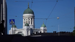 Man with backpack and trolley case come across street against Helsinki Cathedral Stock Footage