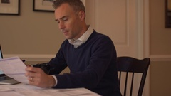 A man going over his bills on his dining room table Stock Footage