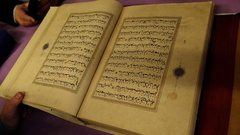 A curator in the National Library presents a rare book in Arabic Stock Footage