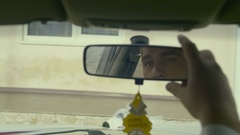 Handsome bridegroom sitting in a car and looking at his reflection in a mirror Stock Footage