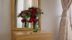 Beautiful bouquet of red flowers on the dressing table near the mirror Stock Footage