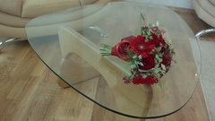 Red bouquet lying on the transparent table glass Stock Footage