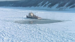 Aerial shot of frozen ship or tugboat staying on river covered with ice in Stock Footage