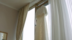 Beautiful White Wedding Gown Hanging by Window Stock Footage