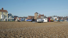 Shingle beach with fishing boats on the foreshore at Aldeburgh Stock Footage