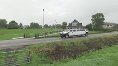 Limousine driving on a dike in Holland, The Netherlands followed by drone Stock Footage
