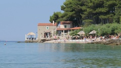 Beach in Bol, Croatia, in summer with people bathing and swimming Stock Footage