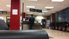 People asking worker question at welcome counter inside Service Canada Stock Footage