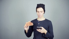 Young man in black knitted hat eating pizza using smartphone gray background Stock Footage