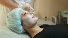 Woman having facial mask at beauty salon. Beauty treatment in spa salon. Stock Footage