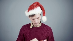 Young man in Santa hat opening a gift box and pulling out an ink pen Stock Footage